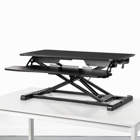 Black stand up desk topper on a stationary side table