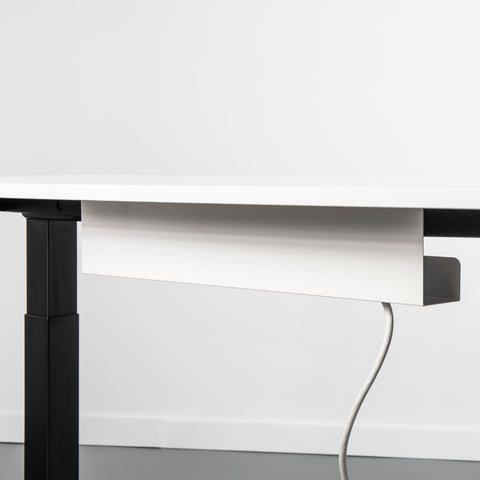 White Cable management holder attached to the underside of a sit stand desk