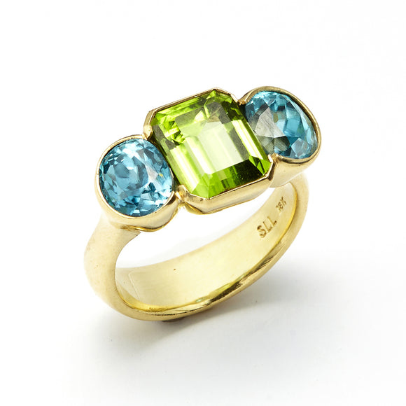 5.8 ct Oval Cut Blue Zircon and 4.07 ct Emerald Cut Peridot Ring set in 18 kt Gold