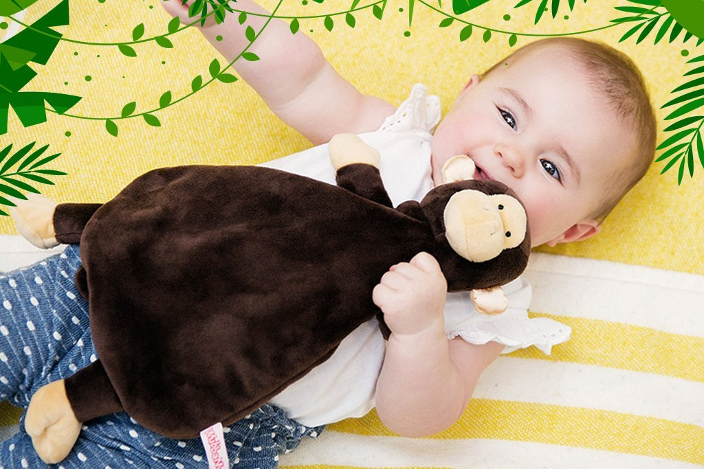 Lovey collection image has a baby holding a brown monkey lovey that has tan accents on face hands and feet