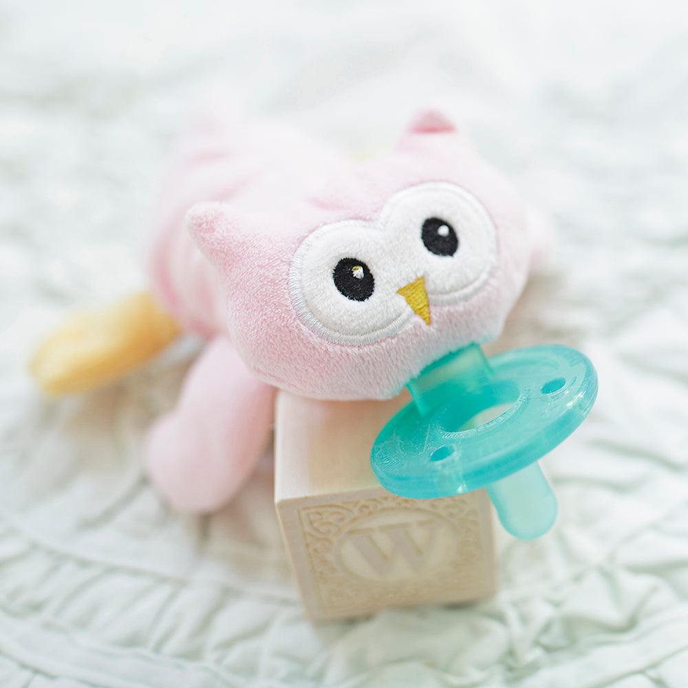 WubbaNub Infant Plush pacifier Pink Owl is soft pink with orange feet and nose and big eyes