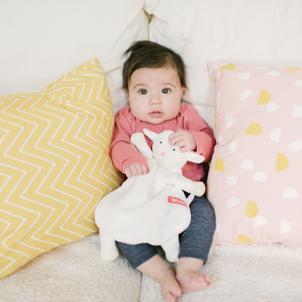Baby holding White Lamb Lovey Blankie with pink nose