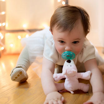 baby with WubbaNub Infant Plush Pacifier Pink Bear is soft pink fabric with white accents on paw pads, ears and face and a brown nose