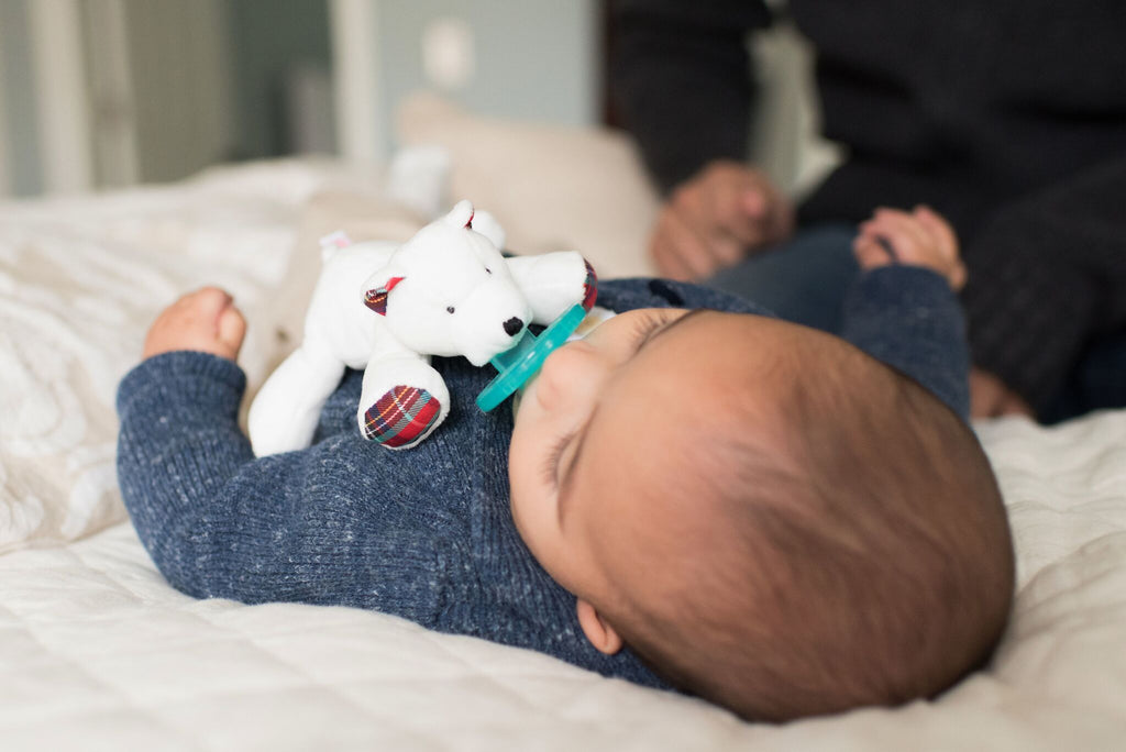 baby using WubbaNub Infant Plush pacifier Polar Bear is a soft snowy white fabric with tartan plaid accents on hoofs and ears