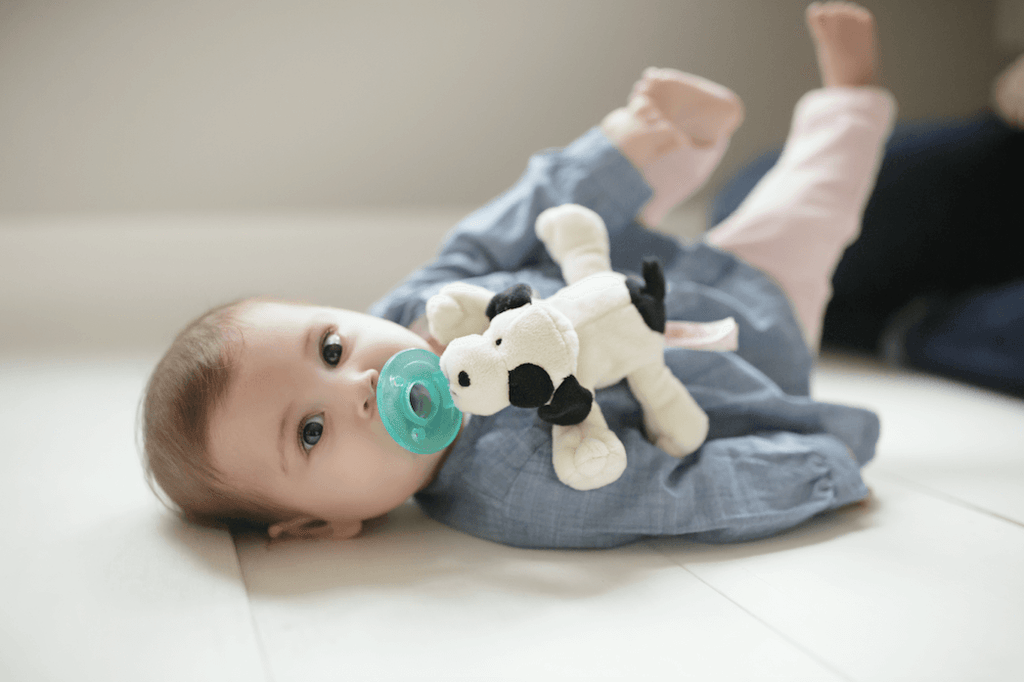Baby with black and white spotted puppy dog wubbanub