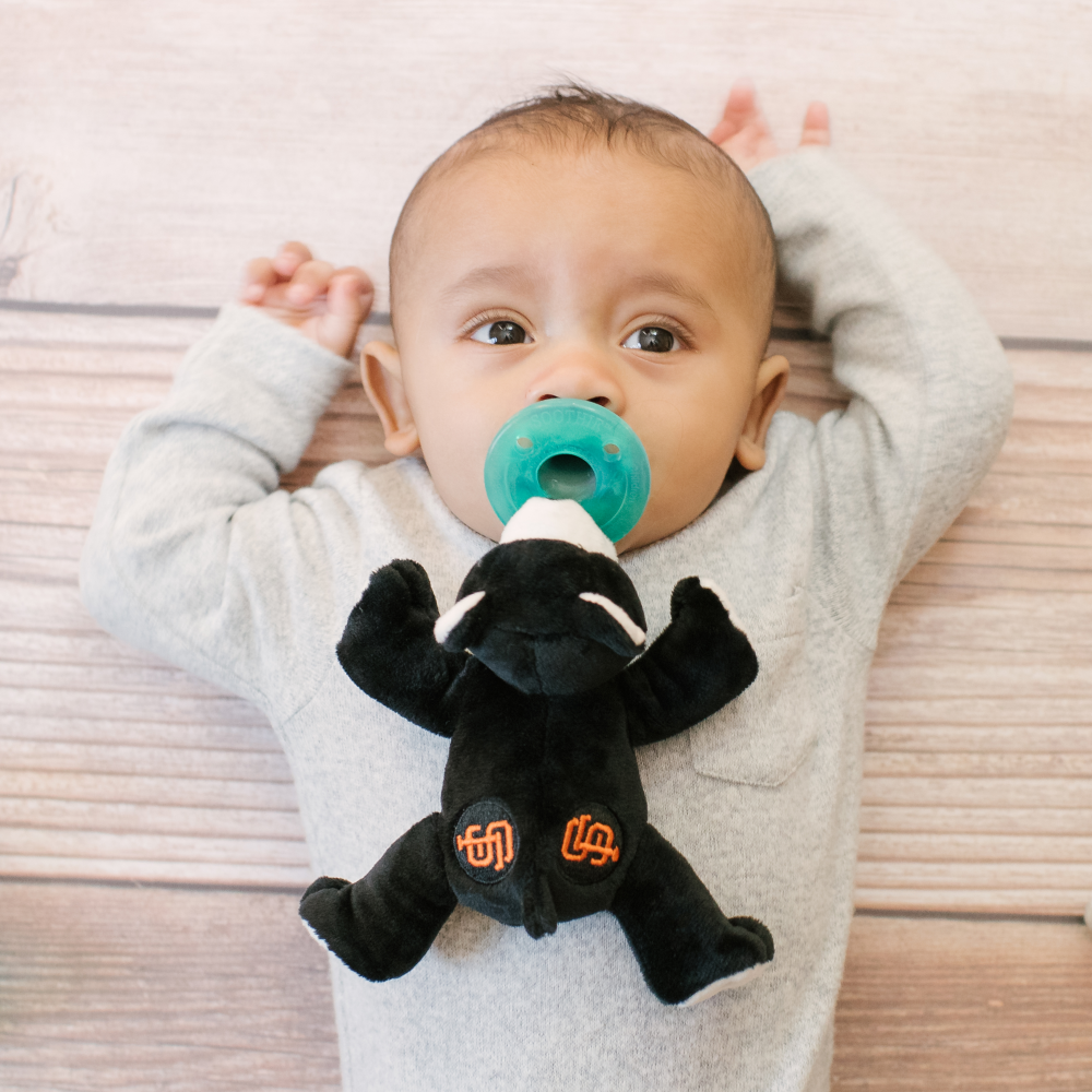 baby with WubbaNub MLB San Francisco Giants Bear is black fabric with white accents on paws, face and ears and has an orange SF emblem on rear