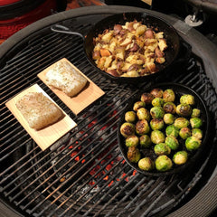 "By Tim Shelburn: ""Surf and turf tonight! Here's two cod pieces on cedar planks with Brussels and red potatoes."" Featuring his cast iron seasoned with Crisbee"