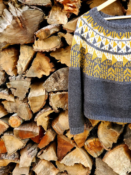 a hand knit colorwork sweater pattern made from American organic cotton + merino wool posed against a wall of firewood