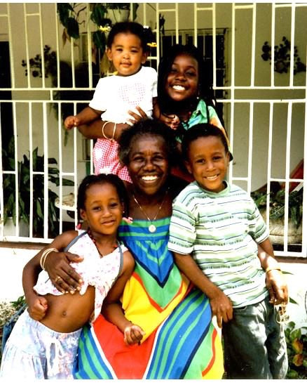 Teju's Jamaican Grandmother along with her young relatives smiling together in a big hug.