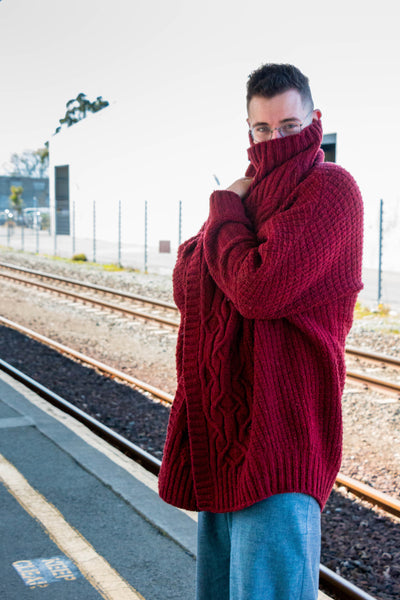A white man with short dark hair wears a red handknit wool cardigan with cables as he playfully hides his face in the high collar