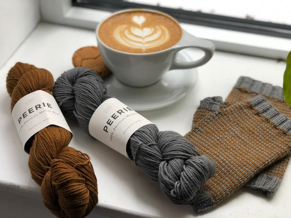 Merino wool yarn Peerie laying by hand knit gloves and a delicious latte in a mug