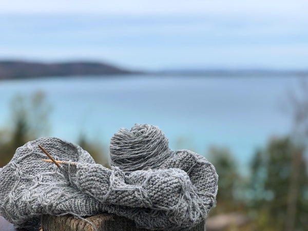 wool yarn WIP in front of a cool blue lake in michigan