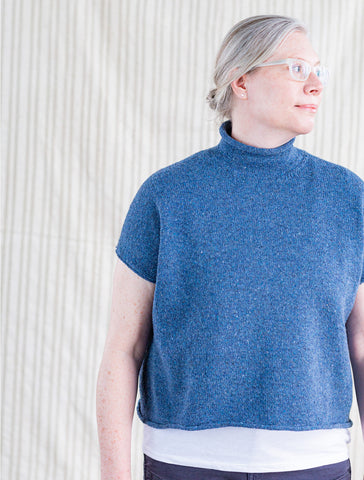 Jen, a woman with short silver hair, wears a blue short-sleeved turtleneck sweater and looks away from the camera to the right.