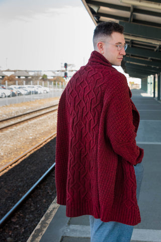 A long red cabled handknit cardigan is worn by a white man with his back turned to the camera, looking over his shoulder