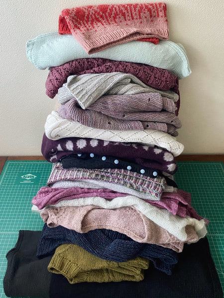teetering pile of hand knit wool pullovers and sweaters