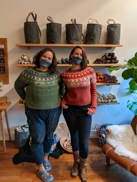 Two women pose in a yarn store wearing matching hand knit colorwork sweaters in two different colors.