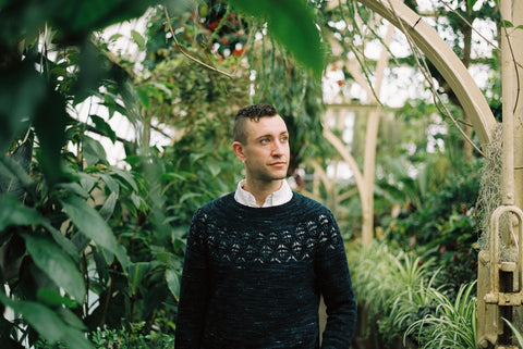 A dark teal handknit sweater with a lace yoke is worn by a white man with dark hair against a background of large plants