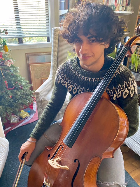 Emanuela's son sits near the Christmas tree in the family home, preparing to play his cello.