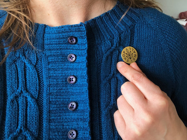 hand knit blue wool sweater sporting a button that reads Shop Small