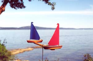 WindRacer Garden Art with Red and Blue Sails on the edge of a lake