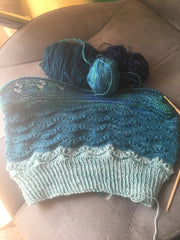 Half-finished knitting with various small balls of teal yarn
