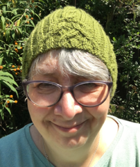 Woman wearing green cabled hat - River Lea Rambles Hat