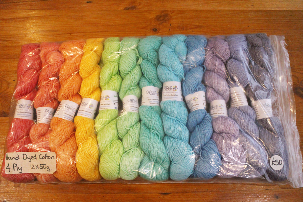 A colourful pack of 12 skeins of 4ply cotton, arranged as a rainbow