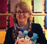 Picture of Deb Cunningham holding a bundle of yarn. Deb is a knitting teacher and host of WoollyAway