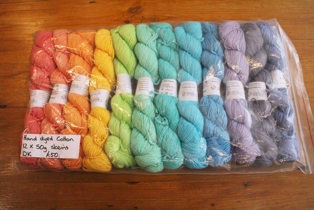 Colourful pack of 12 skeins of cotton yarn arranged in a rainbow