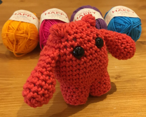 Angus the amigurumi monster strutting his stuff with some balls of Sirdar Happy Cotton