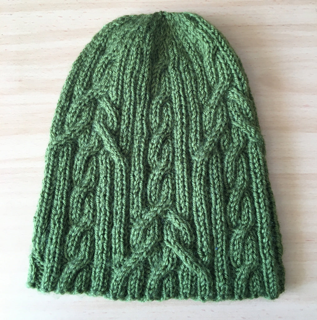 Green cabled hat laid flat on a table