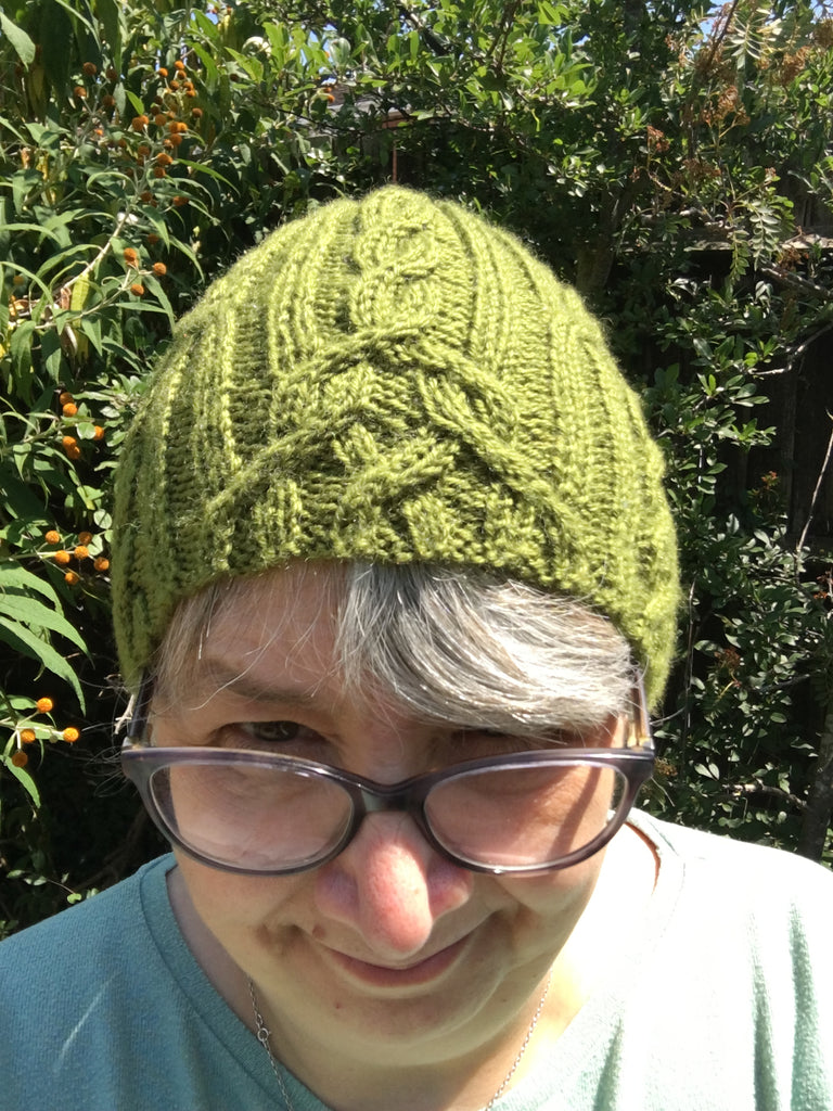 Woman wearing a green cabled hat