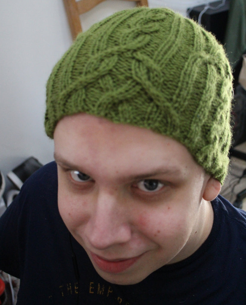 Young man wearing green cabled hat