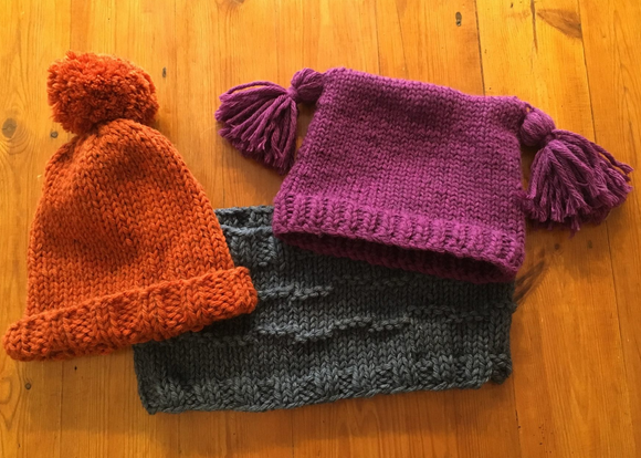 Two hats and a cowl arranged on a table. All of which are included in the workbook for Knitting in the Round Class at Crates of Wool.