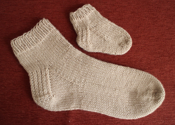 two knitted socks, one baby sized, one adult sized - as learnt at the sock knitting workshop at Crates of Wool