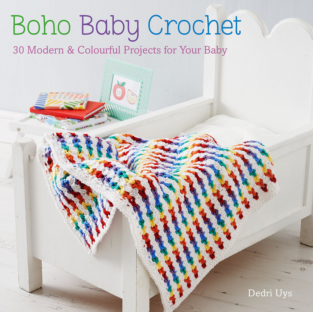 "The front cover of ""Boho Baby Crochet"" by Dedri Uys, with tagline ""30 modern & colourful projects for your baby"". The image depicts a rainbow crocheted blanket over a crib."
