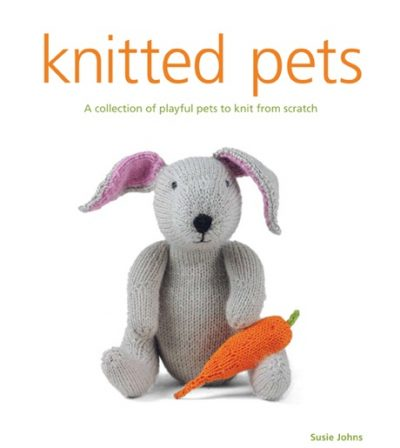 "The front cover of ""knitted pets"" by Susie Johns, with the tagline ""A collection of playful pets to knit from scratch"". There is an image of a knitted rabbit with a carrot."