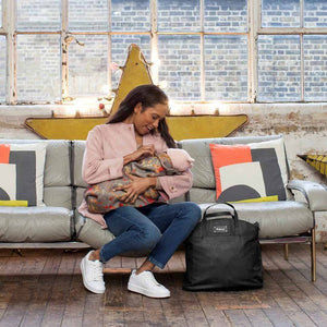 Babymel  changing bag vegan leather, Grace black PU, mum holding baby with bag by her side, faux leather, handbag baby bag