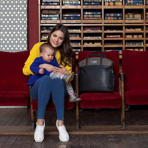 Babymel  changing bag vegan leather, Grace grey PU, mum holding baby with bag by her side, faux leather, handbag baby bag