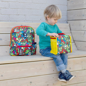 Zip and Zoe by Babymel zipped lunchie and ice pack dino multi, boy sitting next to backpack on bench, holding lunch bag | lunch bag | boys lunch bag | girls lunch bag | ice pack