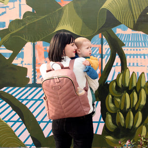 Babymel changing bag backpack, Gabby dusty pink, mum wearing backpack holding baby, pink with gold changing bag, chevron quilt
