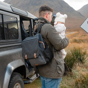 Babymel changing bag backpack, George Black Tweed, dad wearing backpack and holding baby, black unisex changing bag, twin backpack