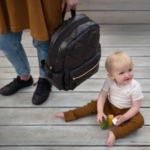 Babymel changing bag, Luna Quilt Black, mum holding backpack and baby sat on floor, black quilted backpack, rucksack baby bag