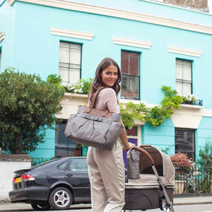 Babymel changing bag Cara grey, mum wearing bag and pushing pram, grey melange changing bag, handbag, shoulder bag.