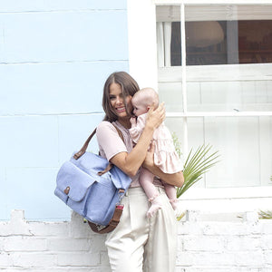 Babymel changing bag, Jade Bluebell, mum wearing bag and holding baby, blue melange, handbag baby bag