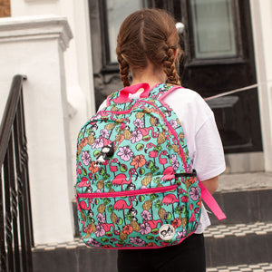 Zip and Zoe by Babymel Junior backpack Flamingo, girl wearing backpack standing in front of front door | school bags for girls | backpacks for girls | kids school bags | kids backpacks