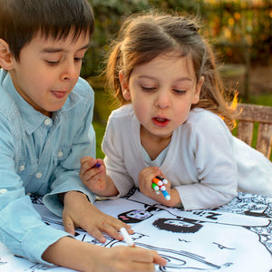 Zip and Zoe by Babymel colour & wash art canvas multi, boy and girl holding washable pens and colouring in art canvas in garden | colour in table cloth | kids colouring