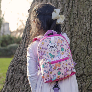 Zip and Zoe by Babymel mini backpack & safety harness-reins llama, girl wearing backpack hiding behind a tree | toddler backpack with reins | toddler rucksack | backpacks for girls | kids school bags | kids backpacks
