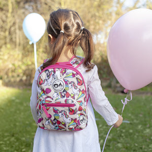 Zip and Zoe by Babymel mini backpack & safety harness-reins unicorn, girl wearing backpack holding balloons in park | toddler backpack with reins | toddler rucksack | backpacks for girls | kids school bags | kids backpacks