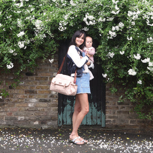 Babymel changing bag, Molly Pink Floral Dot, mum wearing bag and holding baby, laminated changing bag, shoulder bag baby bag